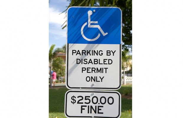 City workers paint a handicapped space around a parked car